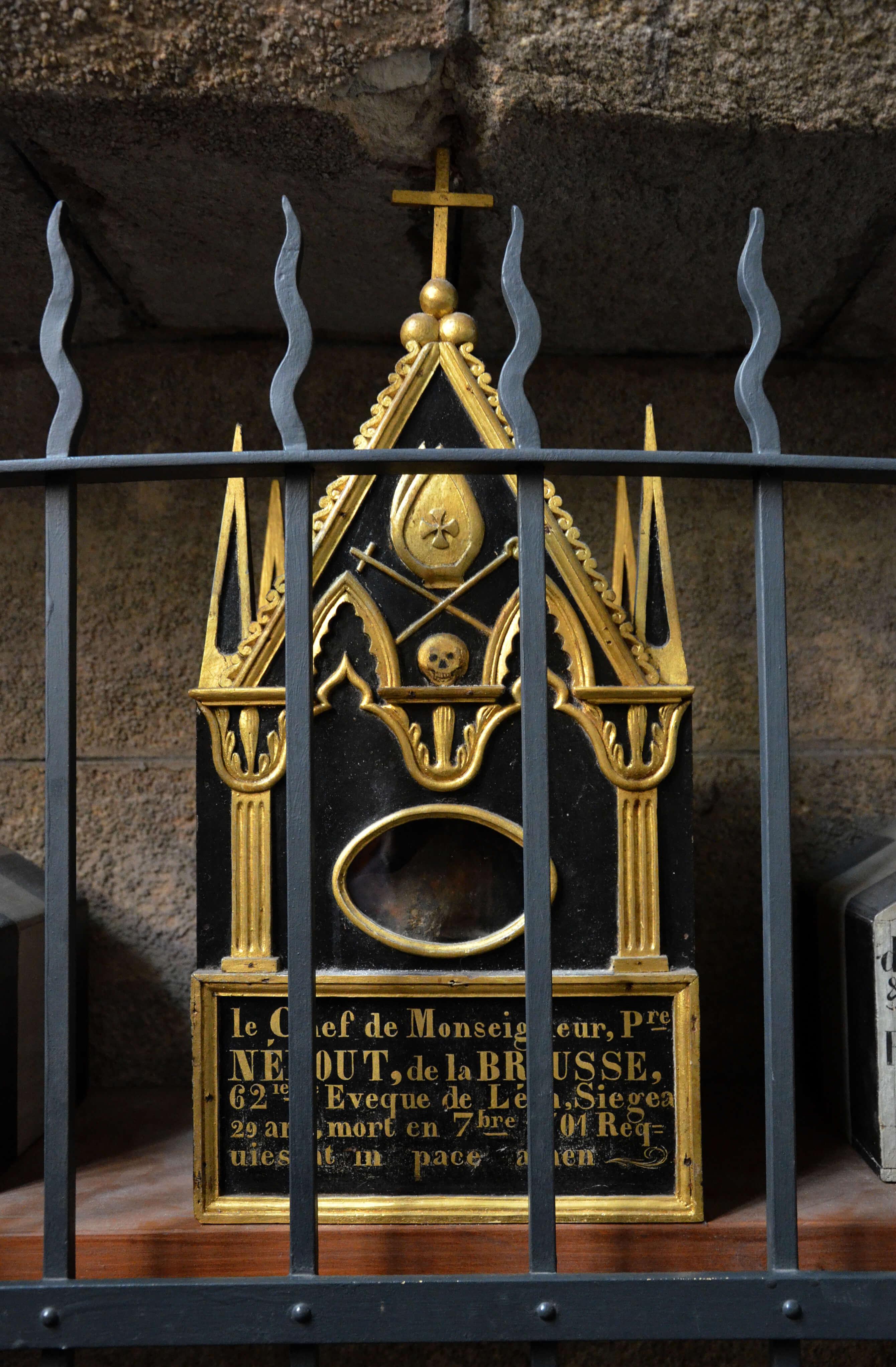 Boîte à crâne noire et richement rehaussée de décorations dorées.